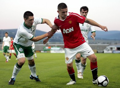 Manchester United's Robert Brady holds off the challenge of Shamrock Rovers' Darren Murray last summer.