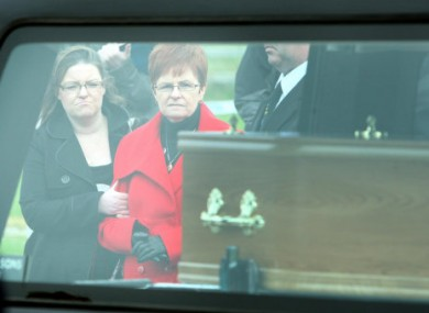 Peter's sister Anne, and her daughter Francis, watch a coffin with Peter Wilson's remains being removed from Waterfoot beach in the Glens of Antrim.