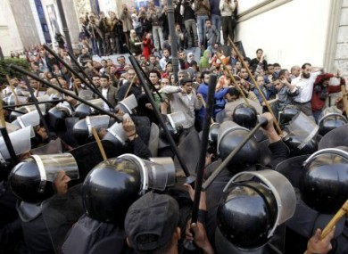 Egyptian anti-riot police confront Egyptian activist outside a journalists syndicate in downtown Cairo, Egypt, Wednesday, Jan. 26, 2011.