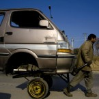 A Pakistani worker transports the front portion of a van on his hand-cart at a road in Rawalpindi, Pakistan on Tuesday.