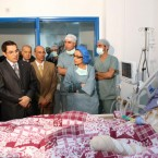 Tunisia's President Zine El Abidine Ben Ali, second left, visits Mohamed Bouazizi, a young man who set himself on fire acting out of desperation after police confiscated the fruits and vegetables he sold without a permit.