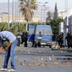 A demonstrator picks up debris as police officers look on in Sidi Bouzid, Tunisia on Monday.