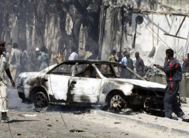 Somali police officers look at the wreckage of a car destroyed in a suicide bombing attack which targeted a police station in southern Mogadishu's Waberi district, Somalia, Monday, Feb. 21, 2011.