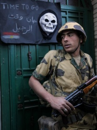 An Egyptian army soldiers stands in front of the Libyan embassy entrance, during a demonstration calling for the ouster of Libyan leader Moammar Gadhafi, in Cairo, Egypt, Monday Feb. 21, 2011.