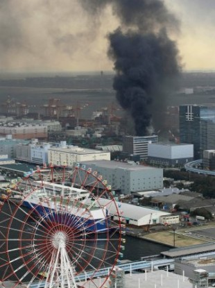 Black smoke rises from a burning building in Tokyo after Japan was struck by a magnitude 8.9 earthquake off its northeastern coast Friday, March 11, 2011.