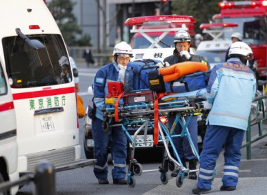 Tokyo Fire Department rescue workers arrive at Kudan Kaikan in Tokyo as local media said its ceiling was damaged after a strong earthquake and injured people inside the hall Friday, March 11, 2011.