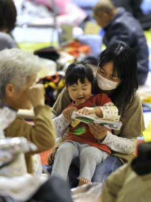A mother and her daughter read a picture book in a shelter in Iwaki, Fukushima Prefecture, on March 14, 2011.