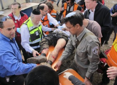 Israeli rescue workers and paramedics treat an injured man after an explosion near a bus stop in Jerusalem, Wednesday, March 23, 2011.
