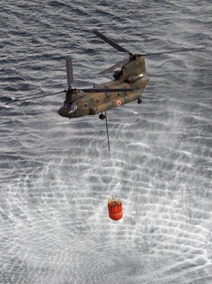 A helicopter scoops water off Japan's northeast coast on its way to the Fukushima Dai-ichi nuclear power plant in Okumamachi Thursday morning.