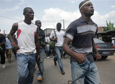 Youths loyal to Laurent Gbagbo carry homemade weapons and a gun.