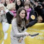 Prince William looks on as Kate Middleton flips a pancake on their first joint official engagement to Northern Ireland. (PA Images/Peter Morrison)