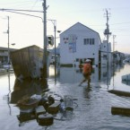A man wades through a flooded street after the tsunami spawned by a powerful earthquake in Iwaki, Fukushima prefecture. (AP Photo/Kyodo News)