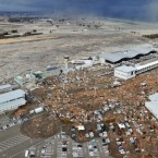 The tsunami spreads across the tarmac and car park at Sendai Airport. (PA Images)