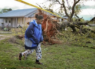 Marice Moorer, whose son and fiance were killed in a tornado in Georgia, walks near a downed tree in Jackson.