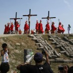 Tourists snap photos as devotees are nailed to the cross<span class=