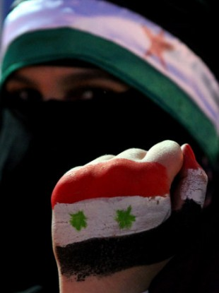 A Syrian protester holds up her hand, painted with the colors of the national flag at a demonstration demanding that Syria's President Bashar Assad step down.