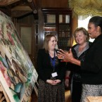 First Lady Michelle Obama with Fionnuala Kenny view an embroidered panel depicting the Norman Invasion during a tour of Farmleigh House.
