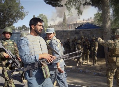 Afghan policemen, U.S. and Afghan soldiers on alert near the police traffic department building, which was under attack by insurgents in Khost, eastern of Afghanistan on Sunday, May 22, 2011.