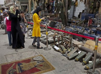 Young women take pictures of spent shells and weapons used during the fighting between the rebels and Moammar Gadhafi forces in Misrata, Libya, Sunday, May 22, 2011.