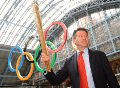Sebastian Coe holds the newly-designed Olympic torch aloft.