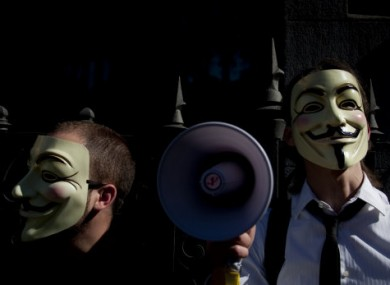 File photo of people wearing masks often used by a group that calls itself
