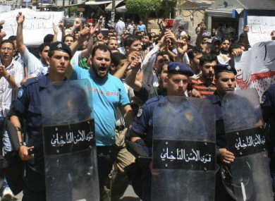 Lebanese riots police officers march in front of anti-Syrian president Bashar Assad protesters, during a demonstration against the Syrian regime, in Tripoli, northern Lebanon, on Friday June 10, 2011.