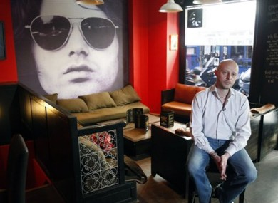 Bar owner Christophe Maillet, 37, speaks during an interview with The Associated Press in his bar, The Lezard King.