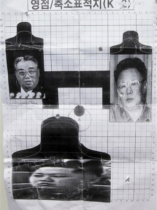 This May 29, 2011 photo shows a firing target depicting North Korea's founder Kim Il Sung, left, leader Kim Jong Il, right, and Kim Jong Il's son Kim Jong Un, bottom, used for reserve forces drills in Seoul, South Korea.