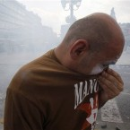 A protestor holds his t-shirt  to his mouth and nose to avoid tear gas. Pic: AP Photo/Petros Karadjias