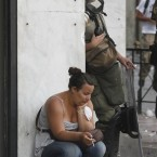 A protester and a riot policeman take a cigarette break together, after clashes during a demonstration in Athens. Pic: AP