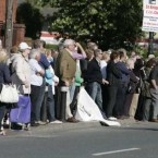 Members of the public wait on Main Street in Blanchardstown Village, for the hearse carrying the coffin of former Minister for Finance Brian Lenihan TD to leave Jennings Funeral Home for St Mochtas Church in Porterstown<span class=