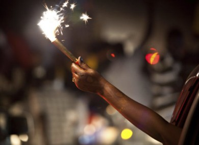 A woman holds a sparkler out of a car window in celebration of South Sudan's impending independence in Juba, South Sudan, late Friday, July 8, 2011.