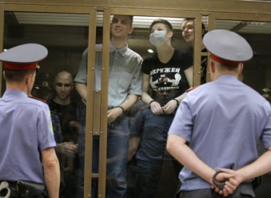 Members of the country's most vicious neo-Nazi gang stands behind a glass wall at a court in Moscow, Russia, July 11, 2011.