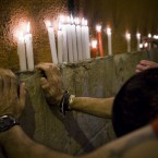 People say good bye with candles as they react in front of a wall, singing the song