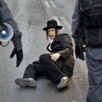 An Ultra-Orthodox Jew falls down while running away from security forces moving in to clear a demonstration against a municipal parking lot that is open on the Jewish Sabbath, in Jerusalem on 16 July, 2011. Ultra-Orthodox activists have repeatedly staged protests since the parking lot opened two years ago, saying operating it on a Saturday is a desecration of the Sabbath, Judaism's biblically-mandated day of rest. (AP Photo/Ben Curtis)