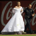 A man who ran onto the field wearing a wedding gown during a baseball game between the Atlanta Braves and the Washington Nationals is led  away by an Atlanta police officer  in Atlanta on 16 July, 2011. (AP Photo/John Bazemore)