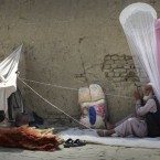 An Afghan street vendor man sells insect nets and brooms, as he twines cord while waiting for customers in Kabul, Afghanistan, on 17 July, 2011. (AP Photo/Musadeq Sadeq)