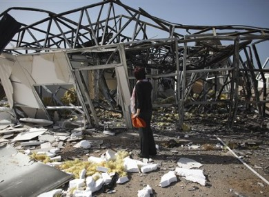 In this photo taken on a government-organized tour, a journalist inspects a building that Libyan officials say was destroyed in an airstrike, near the town of Zlitan.