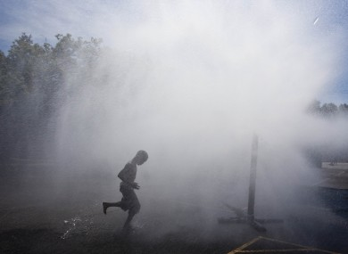 A child cools off in water spray as a heatwave continues in Wisconsin, US.