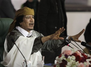 In this Wednesday, March 2, 2011 file photo, Libyan Leader Moammar Gadhafi gestures to supporters as he speaks in Tripoli, Libya.