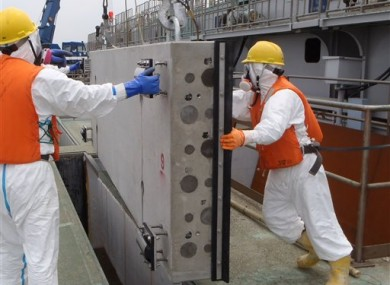 Masked workers in protective outfits prepare to drop one of sliding concrete slabs into a slit of the upper part of the sluice screen for Unit 2 reactor, Fukushima.