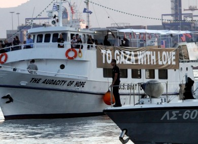 The Audacity of Hope is escorted by the Greek coast guard ship in the town of Perama, near Athens yesterday