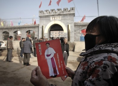 A village woman shows a leaflet with a picture of Bishop Guo Jincai, which was distributed by worshipers after the bishop ordination ceremony in November