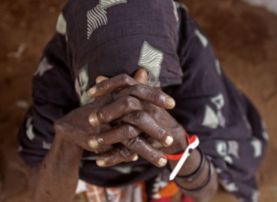 An elderly woman waits inside a food distribution center after being registered as a refugee in Dadaab, Kenya, Monday, 1 Aug, 2011.