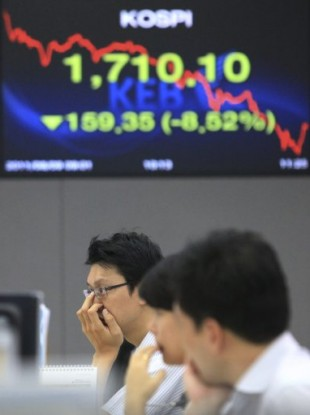 Currency traders work in Seoul, South Korea, Tuesday, Aug. 9, 2011.