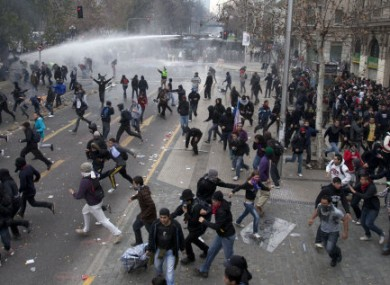 Police fire water cannons on demonstrators trying to reach La Moneda presidential palace during a march on the second day of a national strike in Santiago, Chile.