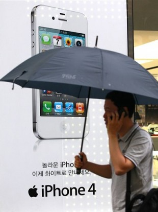 A man passes by an Apple iPhone advertisement at downtown Seoul, South Korea, Tuesday, Aug. 17, 2011.