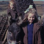 A pair of shy young girls pose for the photographer.  Collecting turf was a job for the whole family.  Photographed in 1963 they show a way of life that existed in Ireland for hundreds of years but is now disappearing.