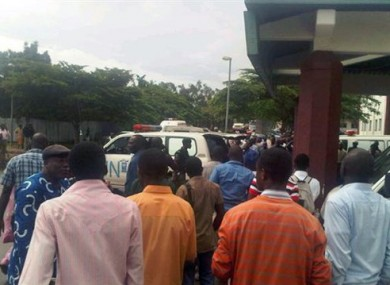 People gather outside a hospital in Abuja today as ambulances arrive after today's explosion.