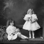 This is in fact brother and sister. Young children were often dressed alike at this time.  Props and poses were used to show whether the child was a boy or a girl  in art and photographs - this boy is standing and has been given a toy animal instead of a doll.